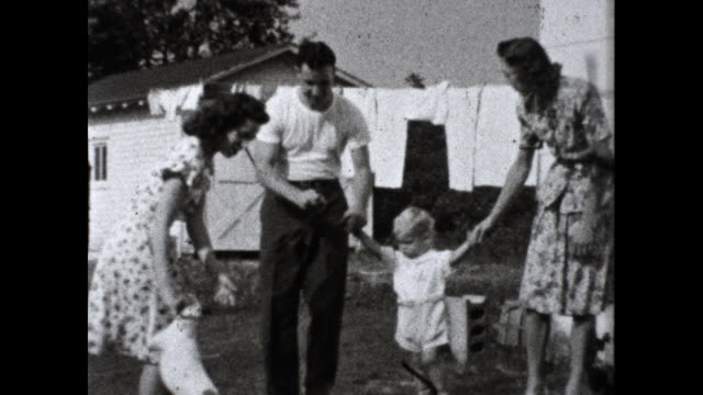 man and woman hold their baby's hands and walk on their lawn towards garden the man walks a dog on a leash and smokes a cigar too a shed and laundry... - two generation family stock videos & royalty-free footage