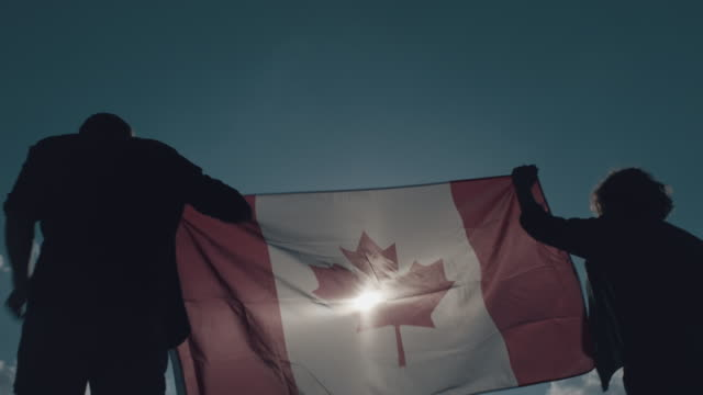 man and woman holding canadian flag - bandiera del canada video stock e b–roll