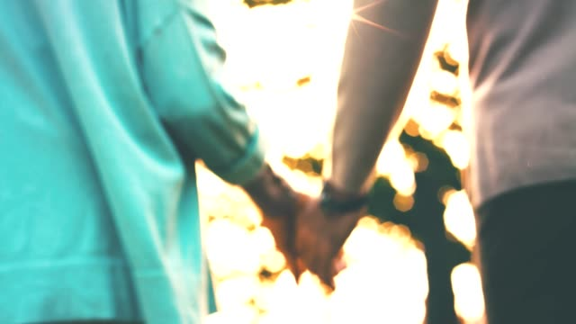man and woman holding hands during sunny day - back lit stock videos & royalty-free footage