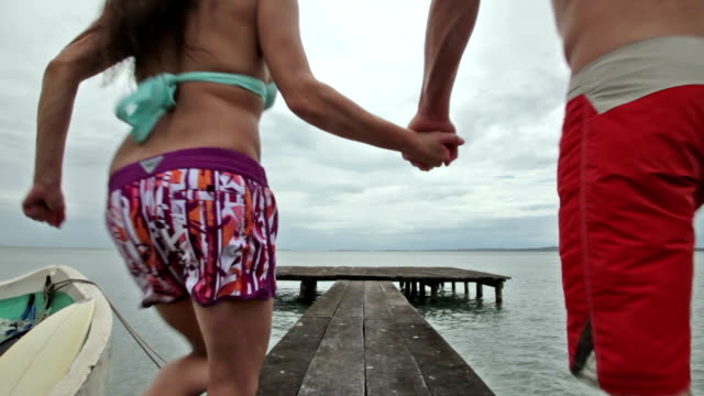 Man and woman holding hands running away from camera jumping off end of dock into ocean.