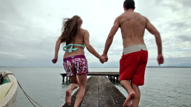 vidéos et rushes de man and woman holding hands running away from camera jumping off end of dock into ocean. - république du panama