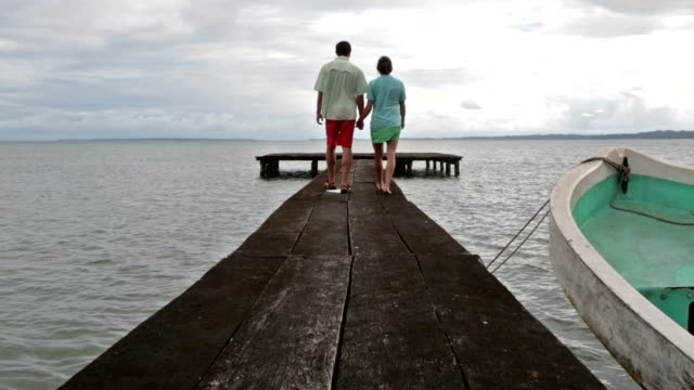 vídeos de stock e filmes b-roll de man and woman holding hands walking away from camera on dock on ocean. - pontão
