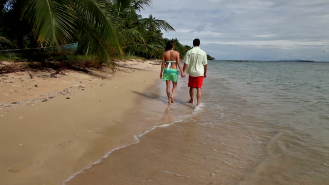 man and woman holding hands walking away from camera on tropical ocean beach. - swimming shorts stock videos & royalty-free footage