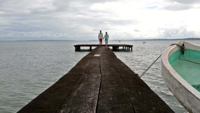 stockvideo's en b-roll-footage met man and woman holding hands walking towards camera on dock on ocean. - mid volwassen koppel