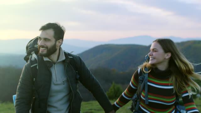 vídeos de stock, filmes e b-roll de homem e mulher segurando as mãos enquanto caminhadas na montanha - longa caminhada