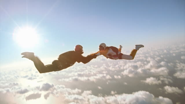 Man and woman holding hands while skydiving