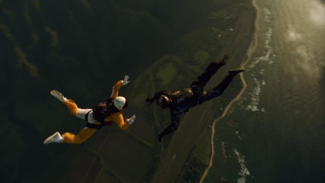 vidéos et rushes de man and woman holding hands while skydiving - parachute
