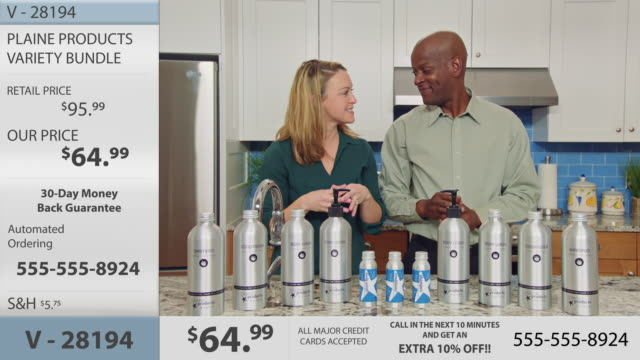 Man and woman hosting infomercial display and discuss a diverse array of eco-friendly body and hair care products in various sizes.