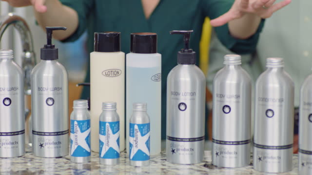 man and woman hosting infomercial highlight a selection of eco-friendly body lotion and hair care products. - hair conditioner stock videos and b-roll footage