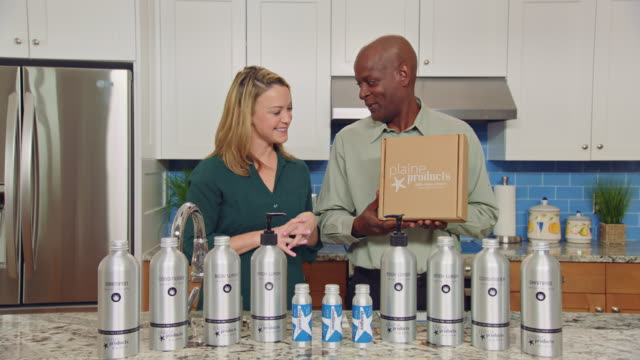 Man and woman hosting infomercial promote the purchase and sustainable return policy of Plaine Products boxes with full retail display.