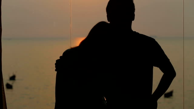 Man and woman hugging and seeing sunset over sea