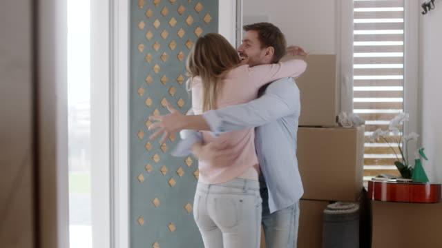 vídeos de stock, filmes e b-roll de homem e mulher abraçando em sua nova casa - casal jovem