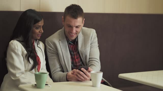 man and woman in a cafe using phones - indian couple tea stock videos & royalty-free footage