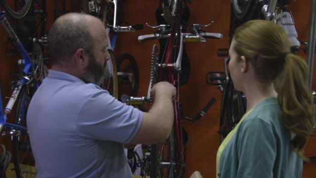 vídeos y material grabado en eventos de stock de man and woman in bicycle shop - cinco objetos