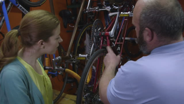 man and woman in bicycle shop - greater london stock videos & royalty-free footage
