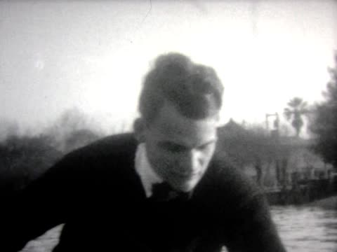 vidéos et rushes de 1928 man and woman in canoe with box camera - 1928