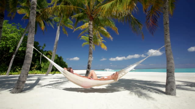 man and woman in hammock on tropical island