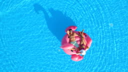 AERIAL: Man and woman in swimsuits laying on fun pink inflatable flamingo float