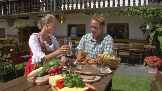 MS Man and woman in traditional dirndl dress drinking beer at lunch table, Bavaria, Germany