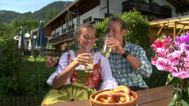 zi cu man and woman in traditional dirndl dress drinking beer in bavarian landscape, bavaria, germany - baviera video stock e b–roll