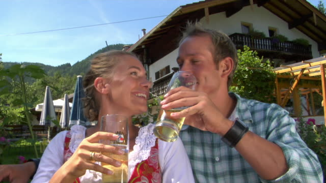 CU Man and woman in traditional dirndl dress drinking beer in Bavarian landscape, Bavaria, Germany