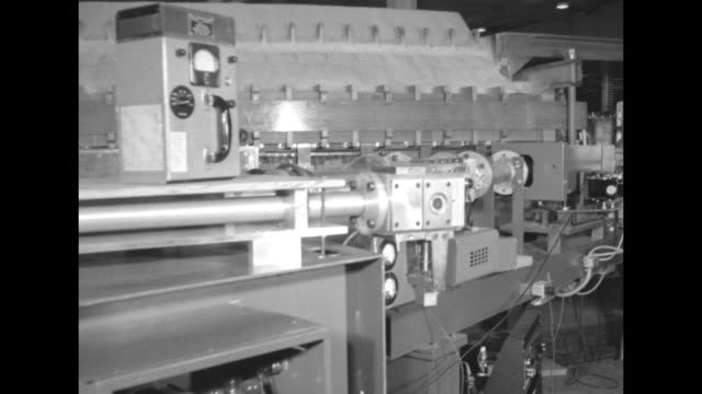 man and woman inspecting cosmotron / cu man's hand turning switch on control board / man and woman inspecting cosmotron / pan across cosmotron /... - physik stock-videos und b-roll-filmmaterial