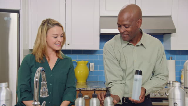 man and woman introduce cleaner and line up body and hair care products for testing in modern kitchen setting on television infomercial. - hair conditioner stock videos and b-roll footage