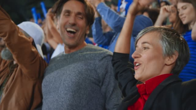 stockvideo's en b-roll-footage met man and woman jumping and cheering on the stadium tribune with the rest of the sports fans - mid volwassen mannen