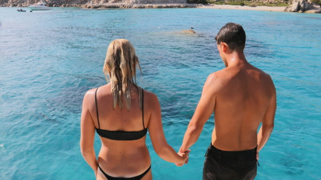 man and woman jumping into sea - swimming shorts stock videos & royalty-free footage