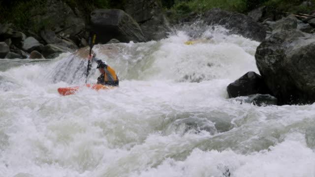ws pan slo mo man and woman kayaking through large rapid waves down river / tena, napo, ecuador - ecuador stock videos & royalty-free footage