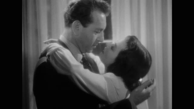 vídeos y material grabado en eventos de stock de 1948 cu - man and woman (paul henreid and joan bennett) kiss as they stand in front of the window at night - blanco y negro
