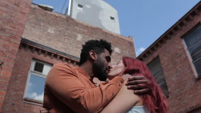 vidéos et rushes de man and woman kissing outside under blue skies in city - embrasser sur la bouche