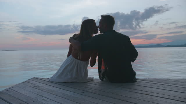man and woman kissing, toasting and drinking a drink at sunset on a tropical island in overwater bungalow hotel resort. - slow motion - hot passionate kissing stock videos & royalty-free footage