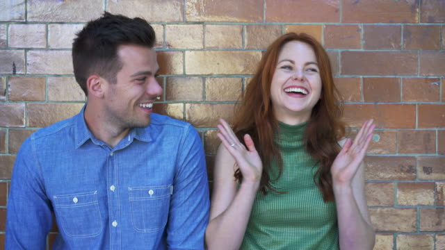 Man and woman laughing, playful, being cute, clapping, agreeing and talking.