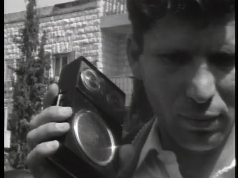 man and woman listen to the adolf eichmann trial on a small radio. - ゲシュタポ点の映像素材/bロール