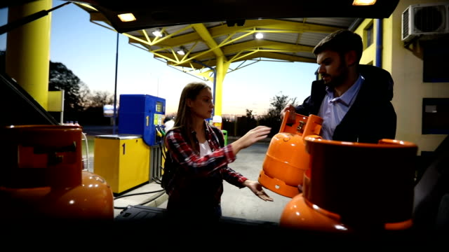 man and woman loading lpg gas bottles in trunk - storage tank stock videos & royalty-free footage