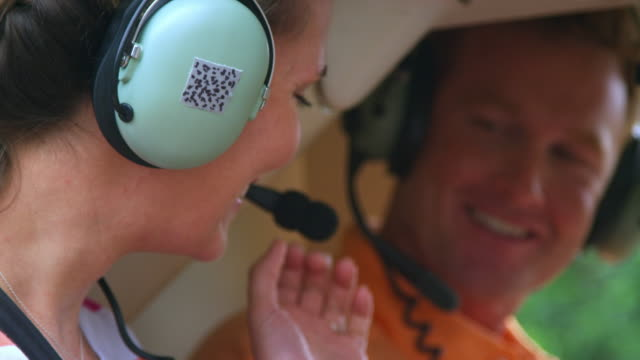 man and woman look at each other and adjust their headphones before taking off in helicopter - helicopter tour stock videos and b-roll footage