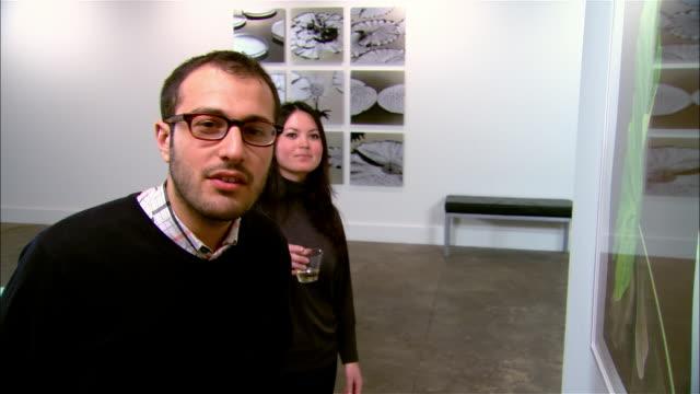 vídeos y material grabado en eventos de stock de man and woman looking at artwork at gallery opening - museo de arte