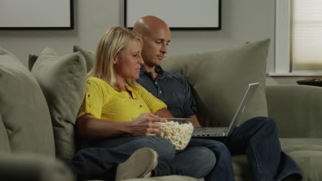 vídeos y material grabado en eventos de stock de ms zi man and woman looking at laptop on sofa / orem, utah, usa - orem