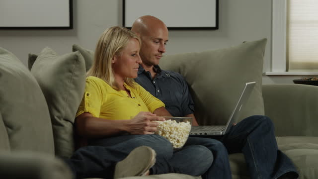 ms zi man and woman looking at laptop on sofa / orem, utah, usa - orem utah stock videos & royalty-free footage