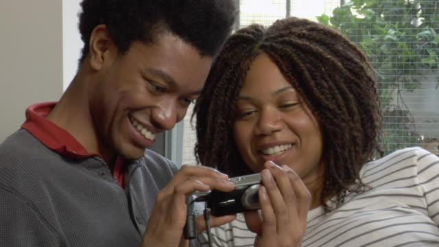cu man and woman looking at photos on digital camera/ new york city - digital camera stock videos & royalty-free footage
