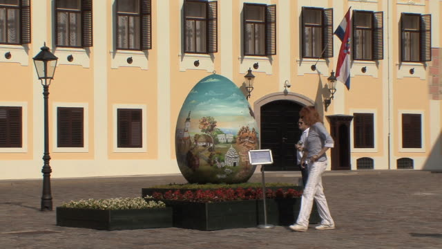 ws man and woman looking decorated eager egg sculpture in st mark square / zagreb, croatia - zagreb stock videos & royalty-free footage
