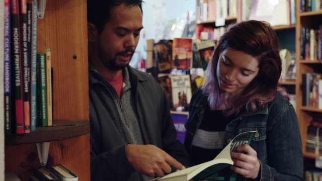man and woman looking through a book in bookstore - bookstore stock videos & royalty-free footage