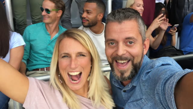 vídeos de stock e filmes b-roll de man and woman making a selfie video dancing on the stadium grandstand and laughing - cabelo louro