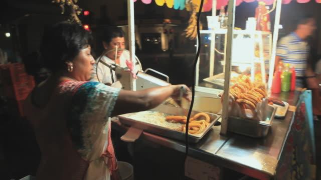 MS Man and woman making churros at food stand, Merida, Yucatan, Mexico