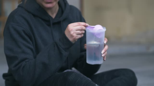 man and woman making protein shake after exercise - shaking stock videos & royalty-free footage