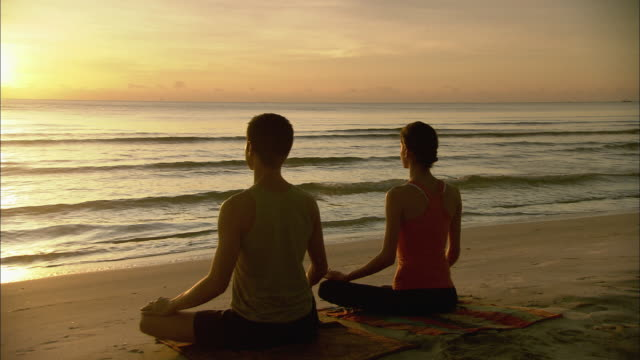 WS PAN Man and woman meditating and sitting in yoga lotus pose on beach at sunrise / Hua Hin, Thailand