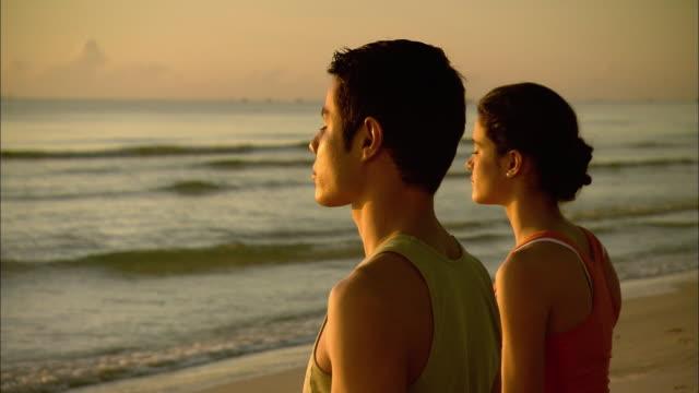 cu man and woman meditating on beach at sunrise, hua hin, prachuap khiri khan, thailand - 横顔点の映像素材/bロール