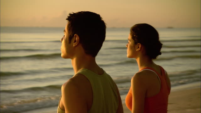 CU DS Man and woman meditating on beach at sunrise, Hua Hin, Prachuap Khiri Khan, Thailand