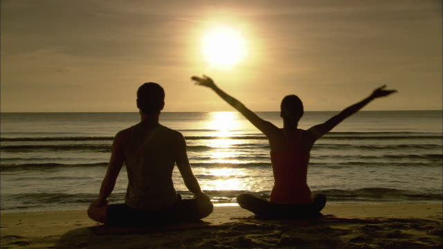 vidéos et rushes de ws man and woman meditating, sitting in yoga lotus pose, and woman stretching on beach at sunrise / hua hin, thailand - technique de relaxation